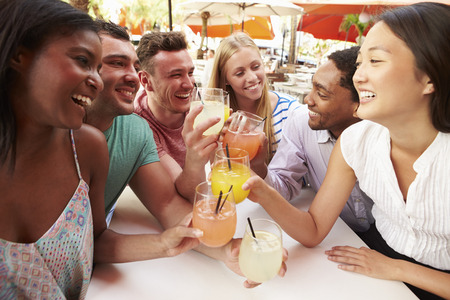 multi cultural: Group Of Friends Enjoying Drinks In Outdoor Restaurant
