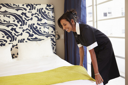 Maid Tidying Hotel Room And Making Bed Stock Photo