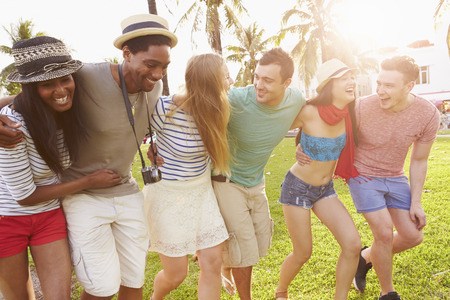 friends having fun: Group Of Friends Having Fun In Park Together Stock Photo
