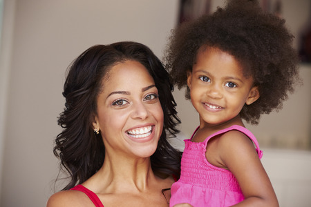 african american mother and daughter: Mother Cuddling Daughter At Home Stock Photo