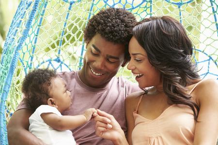 swing seat: Famiglia con il bambino che si distende sulla Outdoor Garden Seat Swing