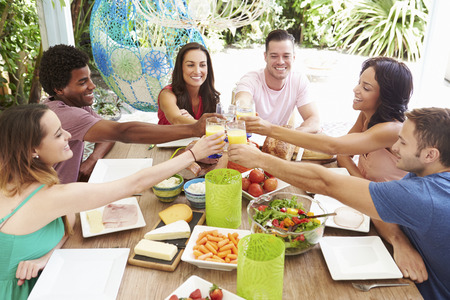 Group Of Friends Enjoying Meal Outdoors At Home photo