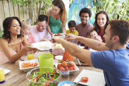 drink food: Group Of Families Enjoying Outdoor Meal At Home