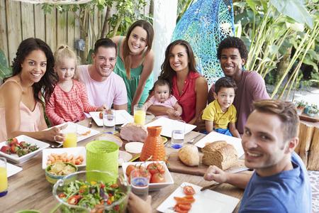 grupo de personas: Grupo de familias disfrutan de la comida al aire libre en el hogar