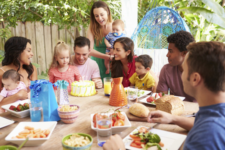 black lady talking: Group Of Families Celebrating Childs Birthday At Home Stock Photo