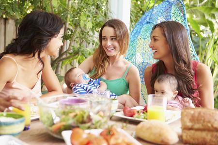 Groep moeders met baby Openlucht Genieten maaltijd thuis Stockfoto