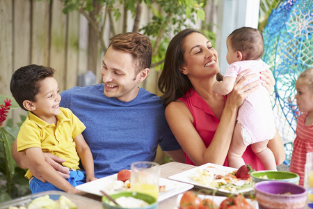 3 6 months: Family Enjoying Outdoor Meal At Home Stock Photo
