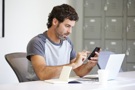 Casually Dressed Man Using Mobile Phone In Design Studio photo
