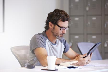 Casually Dressed Man Using Digital Tablet In Design Studio photo