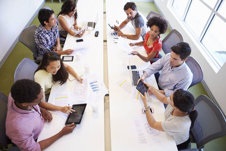 collaborating: Overhead View Of Designers Meeting To Discuss New Ideas