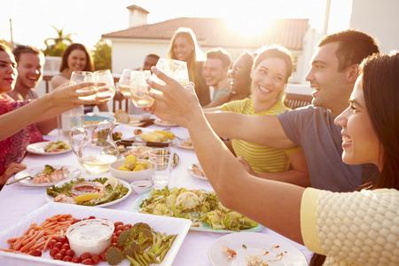 ätande: Grupp ungdomar som tycker om utomhus- Sommar Måltid Stockfoto