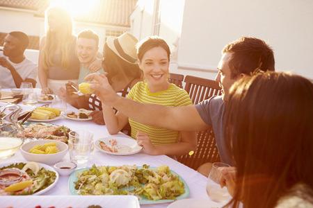 Gruppe von jungen Menschen genießen Mahlzeit im Freien Sommer
