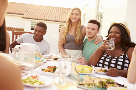 multi ethnic: Group Of Young People Enjoying Outdoor Summer Meal Stock Photo