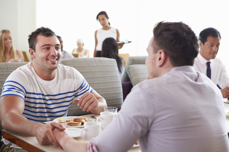 Male Couple Enjoying Breakfast In Hotel Restaurant photo