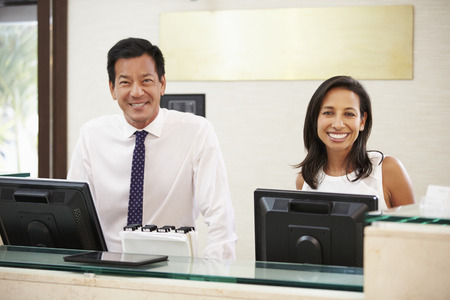front desk: Portrait Of Reception Staff At Hotel Front Desk