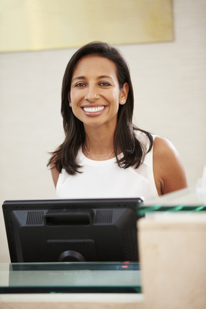 receptionist: Portrait Of Female Receptionist At Hotel Front Desk