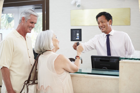 checking in: Senior Couple Checking In At Hotel Reception