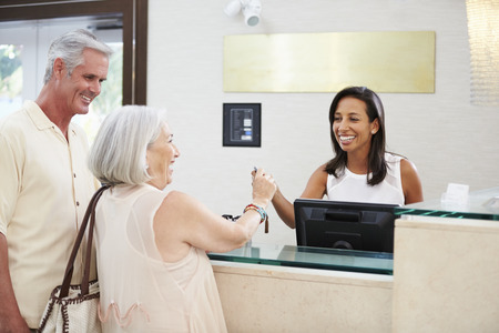 front desk: Senior Couple Checking In At Hotel Reception