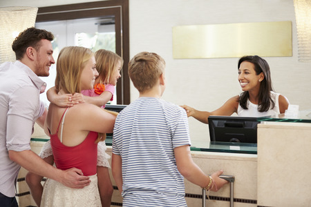 Family Checking In At Hotel Reception photo