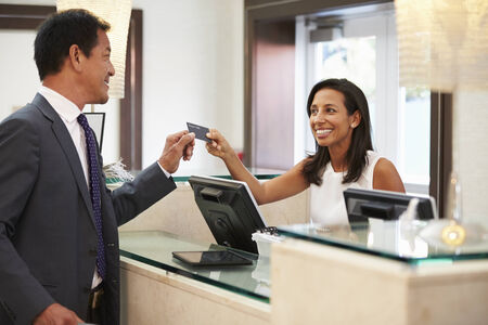 checking in: Businessman Checking In At Hotel Reception Front Desk