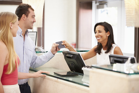 front desk: Couple Checking In At Hotel Reception Stock Photo