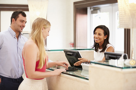 checking in: Couple Checking In At Hotel Reception Using Digital Tablet Stock Photo