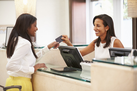 Woman Checking In At Hotel Reception photo