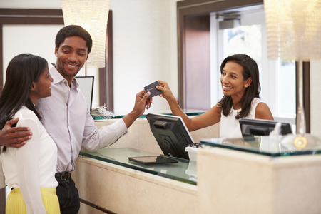 hotel: Couple Checking In At Hotel Reception Stock Photo