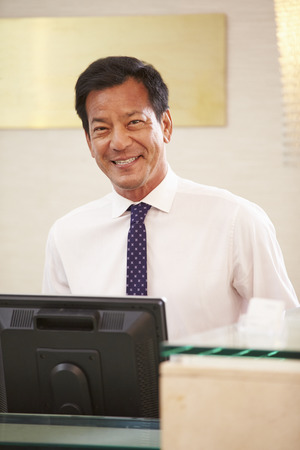 front desk: Portrait Of Male Receptionist At Hotel Front Desk