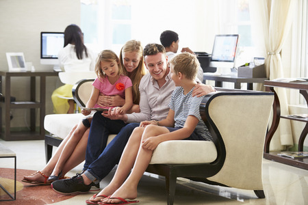 10 years old: Family In Hotel Lobby Looking At Digital Tablet Stock Photo