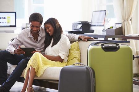 デジタル タブレットを見てホテルのロビーに座っているカップル