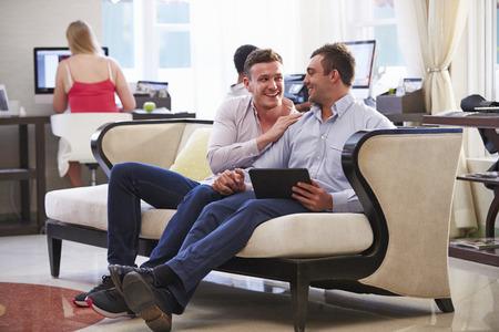 hombres gays: Hombre Pareja Sentada En Lobby del Hotel Mirando a la Tableta digital