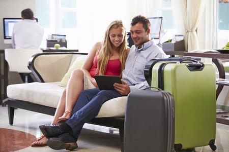 femme valise: Couple Sitting In Hôtel Lobby Regardant tablette numérique