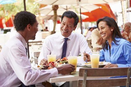 chinese american: Three Businesspeople Having Meeting In Outdoor Restaurant Stock Photo