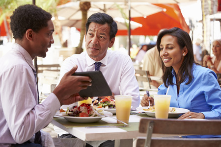 lunch meeting: Three Businesspeople Having Meeting In Outdoor Restaurant Stock Photo