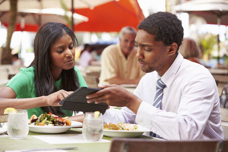 people: Two Businesspeople Having Meeting In Outdoor Restaurant Stock Photo