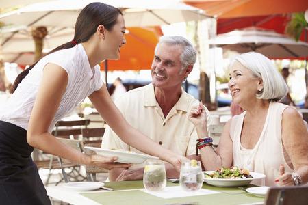 ランチ年配のカップルの屋外レストランでウェイトレス