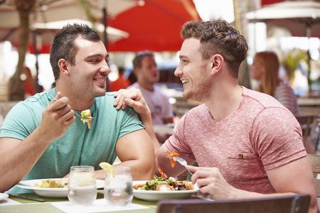 屋外レストランでランチを楽しむ男性のカップル