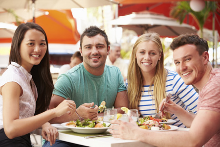 restaurant people: Group Of Friends Enjoying Lunch In Outdoor Restaurant