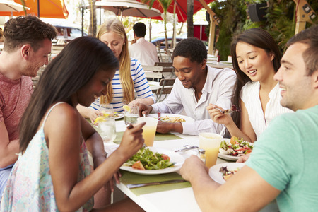 people eating restaurant: Group Of Friends Enjoying Lunch In Outdoor Restaurant