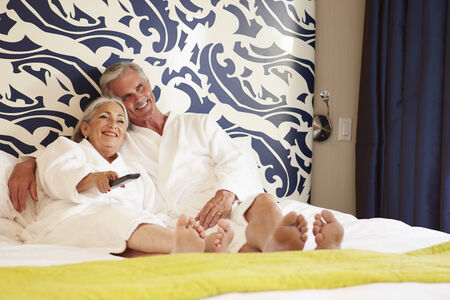 toweling: Senior Couple Relaxing In Hotel Room Watching Television Stock Photo
