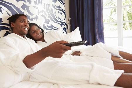 mujer viendo tv: Pares que se relajan en Cuarto de Hotel Televisión de observación