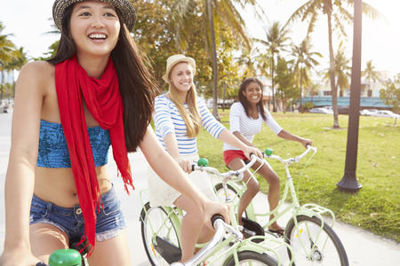 multi cultural: Female Friends Having Fun On Bicycle Ride