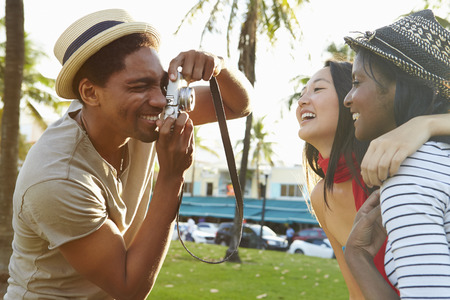asian american: Man Taking Photograph Of Women In Park