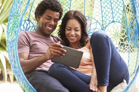 swing seat: Couple On Outdoor Garden Seat Swing con tavoletta digitale