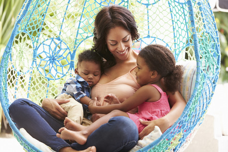 3 6 months: Mother With Children Relaxing On Outdoor Garden Swing Seat