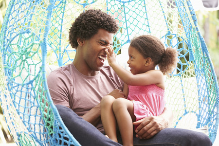 two girls hugging: Father With Daughter Relaxing On Outdoor Garden Swing Seat