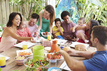 happy black family: Group Of Families Enjoying Outdoor Meal At Home
