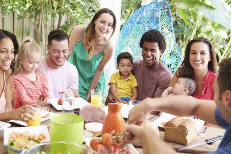 hombre comiendo: Grupo de familias disfrutan de la comida al aire libre en el hogar