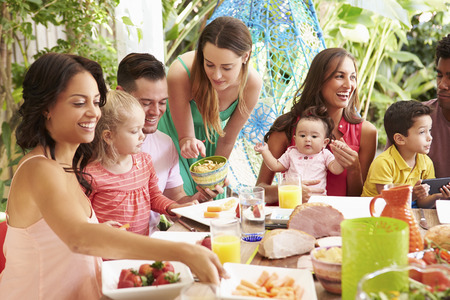 family and friends: Group Of Families Enjoying Outdoor Meal At Home